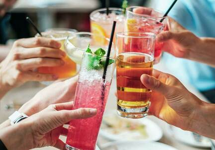 group of hands with alcohol drinks cheers in middle