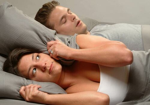 woman lying awake at night frustrated because husband is snoring; pillow around womans ears