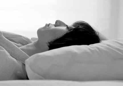 black and white image of woman sleeping on pillow