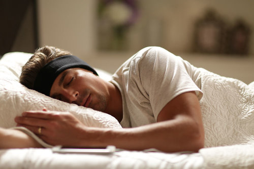man sleeping with black SleepPhones headphones for tinnitus
