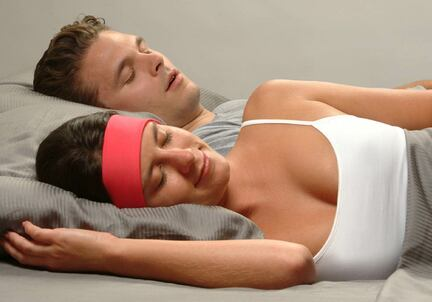 man snoring in background, woman sleeping comfortably with pink SleepPhones headphones for sleeping with a snoring partner
