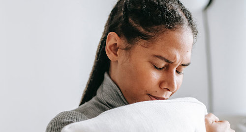 woman clenching pillow upset with insomnia from ptsd