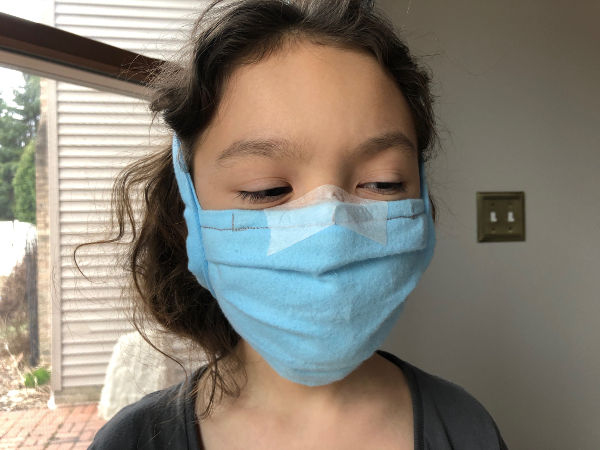 kid wearing a face mask comfortably secured with surgical tape