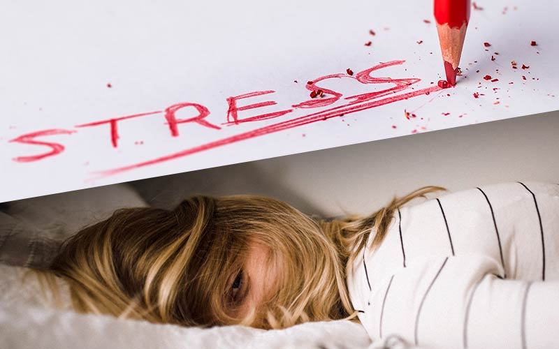 woman laying in bed stressed out she can't sleep with stress written above her in red colored pencil