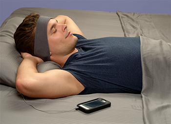 man sleeping with SleepPhone® Classic plugged into his smartphone