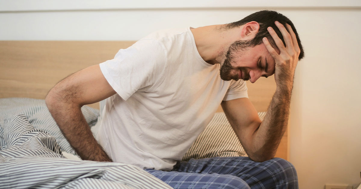 man leaning over with migraine pain